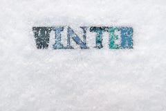 Das Wort WINTER auf einem Schneehintergrund Stockbild