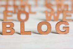 Das Wortblog mit hölzernen Buchstaben auf einem Hintergrund von verwischt ließ Stockfoto