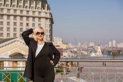 Das wunderbare blonde Modell, das im schwarzen Mantel aufwirft, trägt Sonnenbrille an Lizenzfreie Stockfotografie