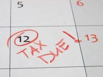 Das Zahlen von Steuerfrist wird mit einem roten Bleistift im Tagebuch markiert lizenzfreie stockfotografie