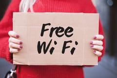 Das Zeichen 'freies Wi-Fi 'in den Händen des Mädchens auf einer Pappplatte stockfotografie