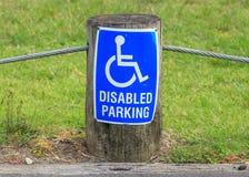 Das Zeichen des behinderten Parkens auf der Straßenseite, nützlich für zusätzl. Stockbild