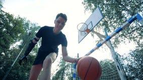 Das Zeitlupejonglieren eines Basketballs führte durch einen jungen Mann mit einer futuristischen Armprothese durch stock video