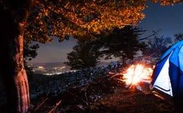 Das Zelt, das in den Bergen mit Stadt kampiert, beleuchtet als Hintergrund Lizenzfreies Stockfoto