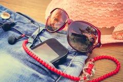 Das Zubehör der Sommerfrauen: rote Sonnenbrille, Perlen, Denimkurze hosen, Handy, Kopfhörer, ein Sonnenhut Getontes Bild Lizenzfreies Stockbild