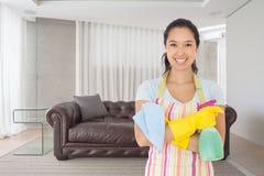 Das zusammengesetzte Bild der Frau stehend mit den Armen kreuzte das Halten von Reinigungsprodukten Lizenzfreie Stockbilder