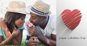 Das zusammengesetzte Bild des glücklichen Paars liegend im zusammen riechenden Garten blüht Stockfotos