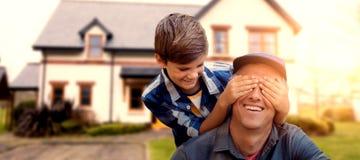 Das zusammengesetzte Bild des kleinen Jungen seine Väter versteckend mustert mit seinen Händen Lizenzfreies Stockfoto