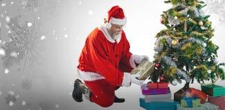 Das zusammengesetzte Bild von Weihnachtsmann Geschenke vereinbarend nähern sich Weihnachtsbaum Stockbilder