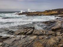 Das Zusammenstoßen bewegt an den felsigen Ozeanklippen wellenartig Stockfotografie