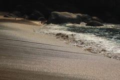 Das Zusammenstoßen bewegt an einem versteckten Strand wellenartig stockfotografie