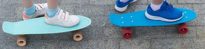 Das zwei Kind-` s fährt, Nahaufnahmen, mit stehenden Füßen auf ihnen Skateboard stockbilder