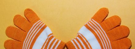 Das zwei Kind-` s Handschuhorange mit weißen Streifen liegt auf der gelben Oberfläche, lizenzfreies stockbild