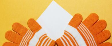 Das zwei Kind-` s Handschuhorange mit weißen Streifen liegt auf der gelben Oberfläche, Stockfoto