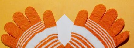 Das zwei Kind-` s Handschuhorange mit weißen Streifen liegt auf der gelben Oberfläche, stockfotografie