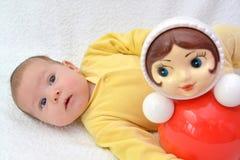 Das zweimonatige Baby liegt nahe einem Puppentrommelspielzeug auf einem weißen Hintergrund Lizenzfreies Stockfoto