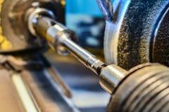 Das zylinderförmige Teil des Eisens wird an einer Schleifmaschine, Nahaufnahme angebracht stockfoto