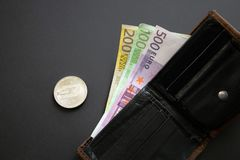Dash coin next to Euro bank notes sticking out of a wallet on black background. Digital currency, block chain market. Euro bills. Next to crypto coin stock images