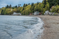Dash Point Shoreline 2. Small waves ripple toward shore at Dash Point Washington. Homes sit under lush green trees as Spring erupts in the Pacific Northwest stock photos