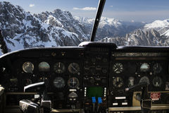 Dashboard in airplane cockpit and mountains view. Air transport, travel, technology and aviation concept - dashboard in airplane cockpit and view of snowy alps Stock Photos