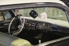 Dashboard of American 60s car with hanging dice stock image