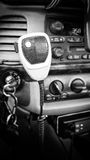 Dashboard Microphone. Car dashboard microphone with cord and radio in background. Keys in the ignition. Clock displayed on the radio Stock Photos