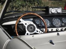 Dashboard of an old british classic car . Particular view of steering wheel and vehicle instrument pane. L . The car is a Triumph TR3 model produced between 1955 Royalty Free Stock Photos