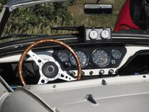 Dashboard of an old british classic car . Particular view of steering wheel and vehicle instrument panel. The car is a Triumph TR3 model produced between 1955 Royalty Free Stock Images