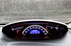 Dashboard and rain droplets on car windshield Stock Images