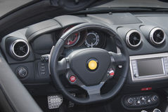 Dashboard and steering wheel. Modern gray dashboard to exotic italian sportscar royalty free stock photography