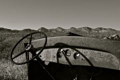 Dashboard and steering wheel of an old truck. Dash and steering wheeling is all which is left of an old truck in the desert. black and white Stock Photos