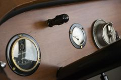 DASHBOARD OF WOODEN BOAT WITH GAUGES. The dashboard of a wooden boat shows the pilot a couple of gauges to operate the boat royalty free stock photography