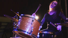 Dashing girl with flowing hair percussion drummer performing with drums. Horizontal stock image