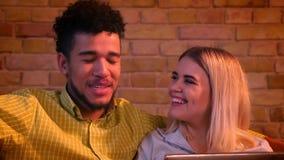 Dat van Afrikaanse kerel en Kaukasisch meisje die met laptop wordt geschoten zijnd thuis gelukkig en ontspannen close-up lachen stock footage