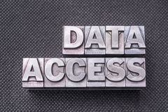 Data access bm. Data access phrase made from metallic letterpress blocks on black perforated surface Stock Image