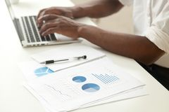 Data analysis and business statistics concept, african-american. Businessman using laptop analyzing work result infographic stats graphs and charts, making Stock Images