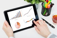 Data analysis concept shown on a tablet held by a woman. In a natural light stock photo