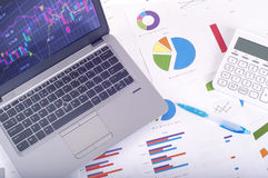 Data analysis - workplace with business graphs and charts, laptop and calculator. Bright stock images