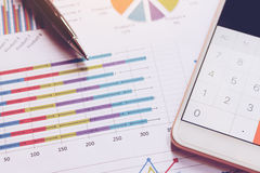 Data analyzing with calculator in smart phone and pen on charts royalty free stock images