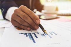 Data analyzing. Close up of business man adviser using pen point Royalty Free Stock Photography