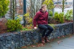 Data aspettante del ragazzo teenager triste che si siede dissatisfi all'aperto di sensibilità fotografie stock