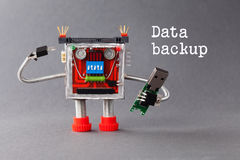 Data backup concept. Robotic character with portable usb device flash stick. Macro view, gray background Royalty Free Stock Photography