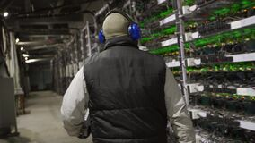 Data center diagnostics technician walks along the mining equipment racks in server room. Network administrator checks
