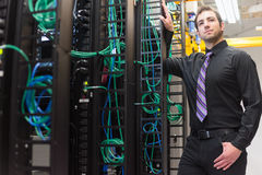 Data center manager. A confident data center manager posing in front of the data center equipment racks royalty free stock photography
