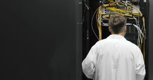 Male server engineer walks through working data center full of rack servers stock footage