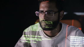 Data code reflection on programmers face. Hackers in glasses hacking programm code at night.