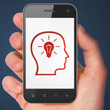Data concept: Head With Lightbulb on smartphone. Data concept: hand holding smartphone with Head With Lightbulb on display. Mobile smart phone in hand on Blue Stock Photo