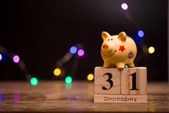 Data de calendário do final do ano financeiro, o 31 de dezembro com o mealheiro no fundo escuro com festão imagem de stock royalty free