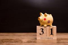 Data de calendário para o fim do exercício orçamental, o 31 de dezembro com o mealheiro no fundo escuro imagens de stock royalty free
