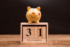 Data de calendário para o fim do exercício orçamental, o 31 de dezembro com o mealheiro no fundo escuro imagens de stock